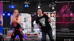 Capture d'une vidéo sur Facebook : derrière le podium de Just Dance à Troyes, le stand de Just Find avec J.R.